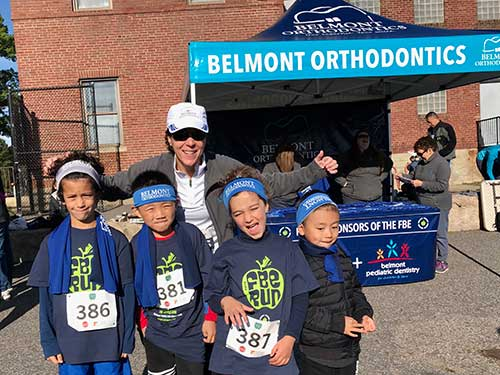 young kids standing together in front of Belmont Orthodontics Sponsor Tent